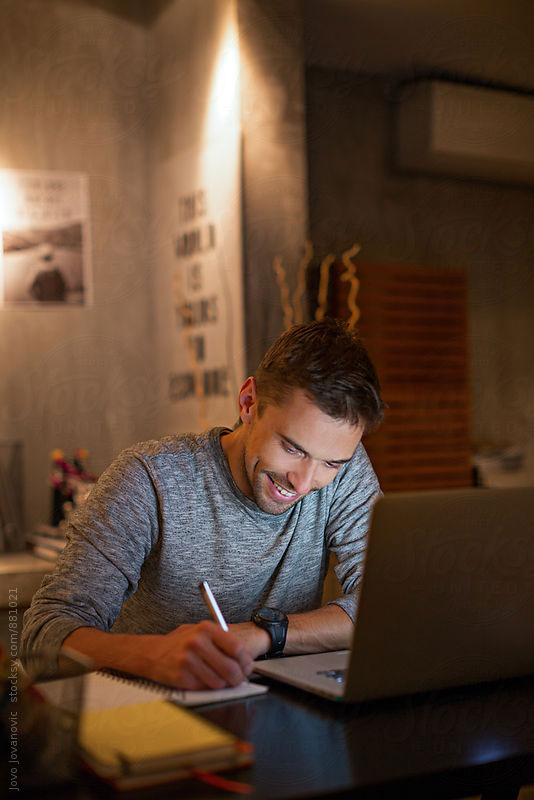 Young man smiling and looking down at his desk working