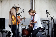 Performers from Port Fairy Folk Festival playing guitar on stage