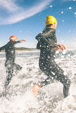 Two men in wetsuits running into the ocean waves