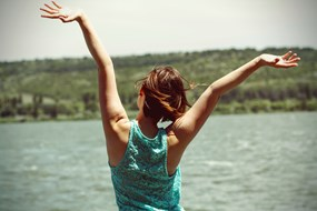 A happy woman with hands in the air by a lake