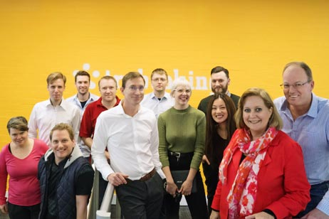 A group of team members in front of a yellow wall