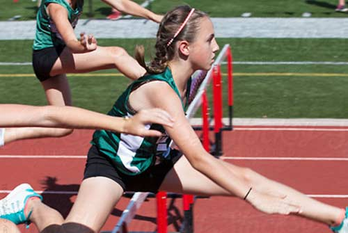 Girl jumps hurdle in running race event
